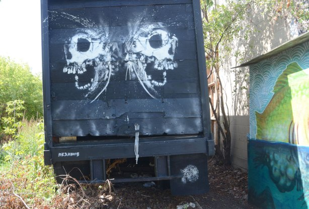 on the back of a truck, two white skulls with wide open mouths in profile, a raccoon and all signed by deadboy.