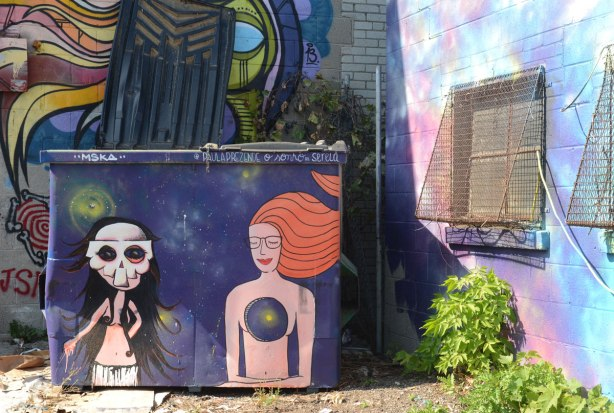 two women painted on a purple dumpster. The one on the left is by mska and the woman has a skull mask on. The other is by paula prezende and is a woman with long red hair but with a big hole in her chest.