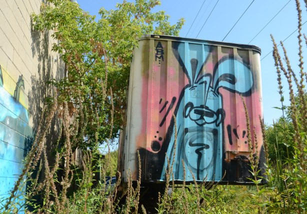 Poser bunny in blue on pink and black background, painted on the back of an old truck container. Weeds growing in front and a tree to the left.