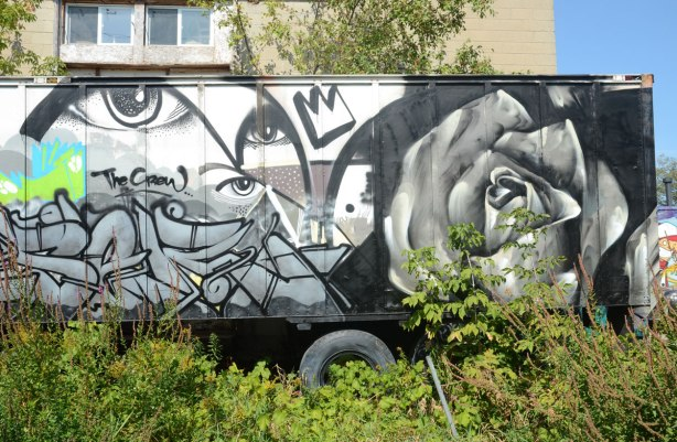 graffiti on the side of an old truck container on wheels that is parked where the weeds are growing up around it. There is a large rose painted in grey tones as well as a black and white piece by The Crew