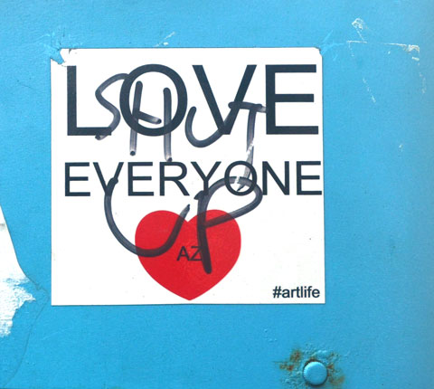 A sticker with a red heart and the words Love Everyone that someone has scrawled on in black marker, shut up
