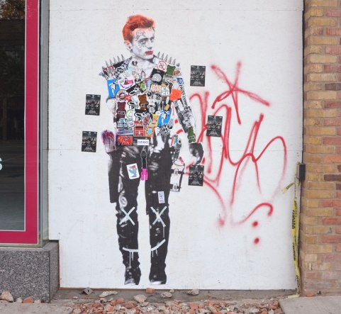 A partial painting of a red head man, life size or close to it, on a white wall that people have added stickers to. The stickers cover all of his torso