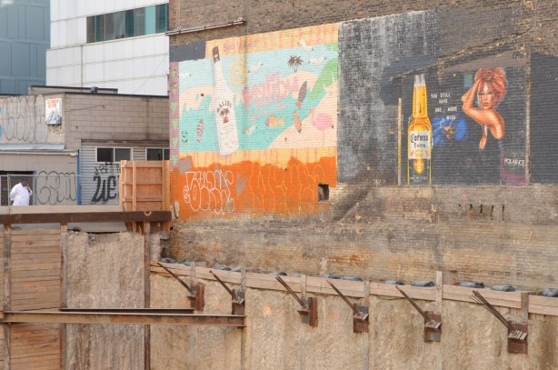 A construction site. A wall has been exposed that has two large wall paintings, one is an ad for Malibu rum and the other is an ad for Corona beer.
