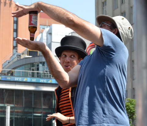 A busker, Funnykito, has a volunteer on stage, The man (volunteer) is holding a beer bottle upside down between the palms of his two hands