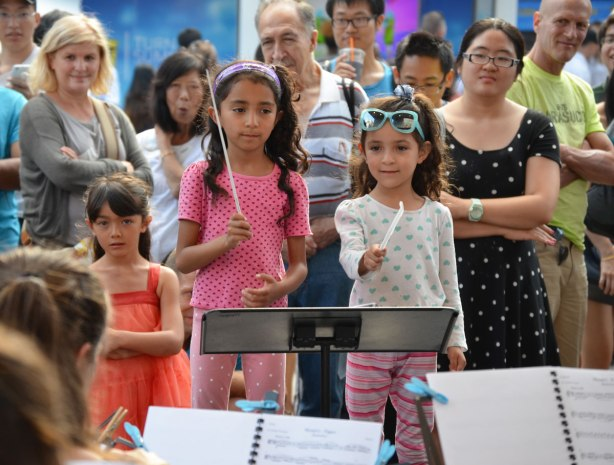 Two young girls take a turn at conducting a small group of musicians playing string instruments at an outdoor festival