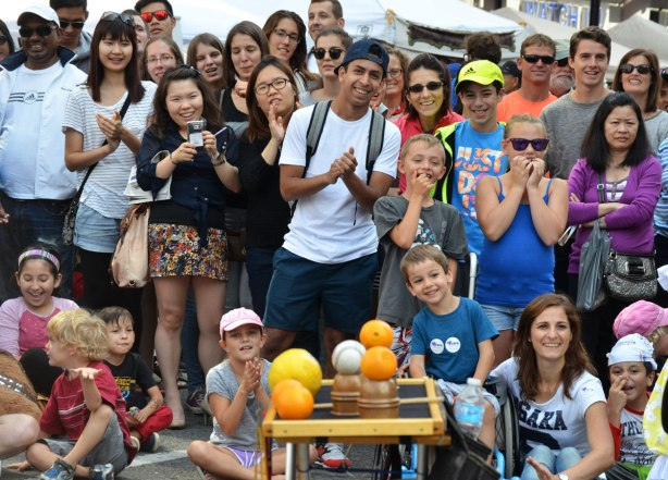 A picture of the crowd watching a show at buskerfest, they are smiling and clapping. A small table with some oranges and a baseball is the foreground, part of the equipment used by Max T. Oz