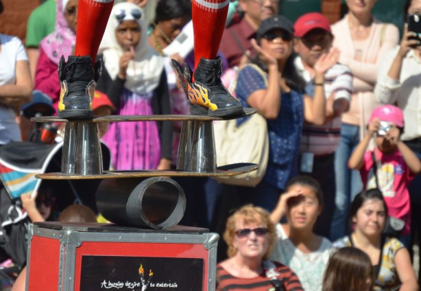 In the foreground is a close up of the busker Fireguy's feet as he stands on a skateboard that is balancing on a large tube, all on top of a box. On the box is written the words 'A burning desire to entertain'. Many people are watching the show.