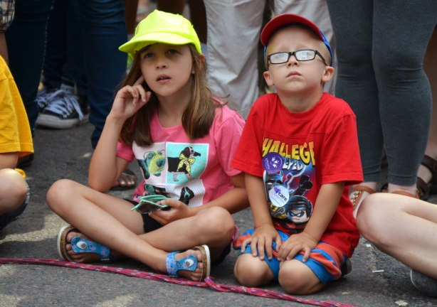Two kids, boy and a girl, sit on the pavement while they watch a performer at an outdoor busker festival