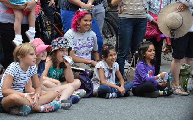 A woman with part of hair dyed a bright pink colour sits with a group of kids on the pavement, others stand behind them. They are all watching a performance at a street festival