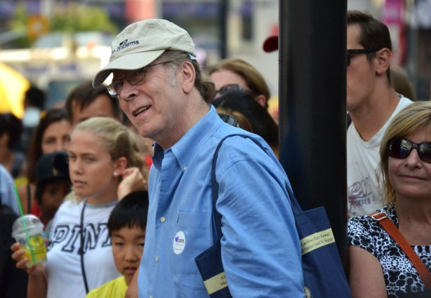 A man in a blue shirt and beige baseball cap watches in fascination at a performance at a street festival. There are other people in the crowd around him.