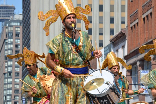 Men on stilts, wearing large gold hats and gold and green costumes, play drums as they walk on stilts above the crowds on Yonge St.