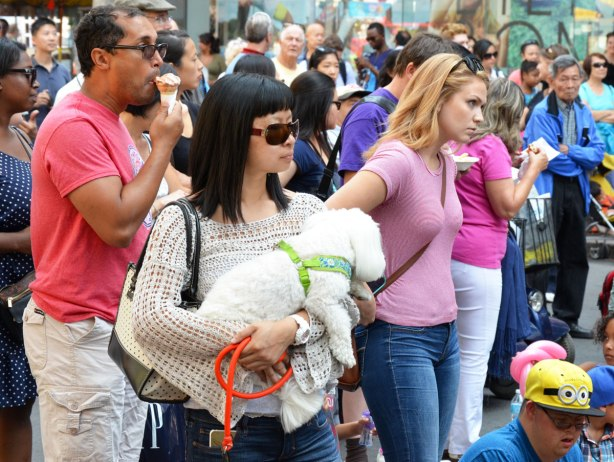 A woman with long dark hair and sunglasses is holding a small white dog