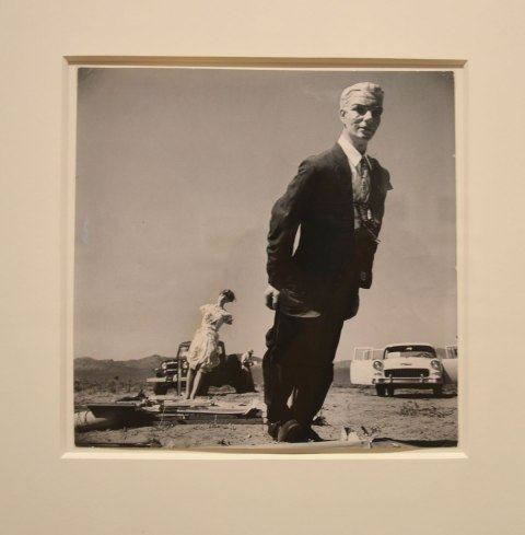 Picture of a black and white silver gelatin print from 1955 by Dean Loomis showing a male mannequin in a black suit who has been partially knocked over by a nuclear test blast in the Nevada desert.