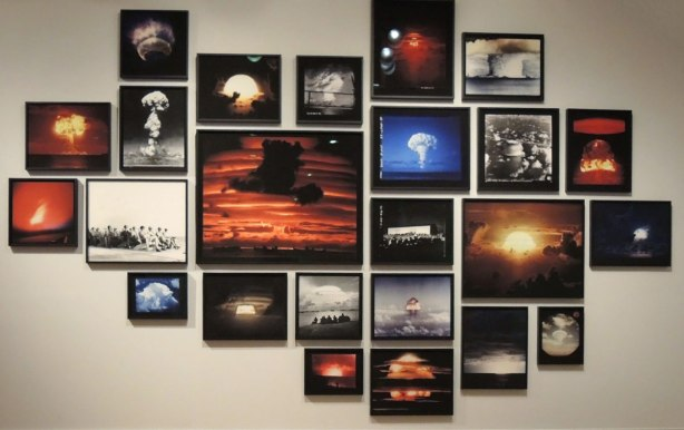 A collage of photos of nuclear blast mushroom clouds. There are about 25 colour and black and white photos hanging on a wall of the Art Gallery of Ontario