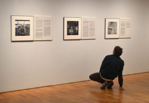 A young man is half squatting as he leans back to get a better look at the words on the wall of an art gallery that accompany three black and white photographs.