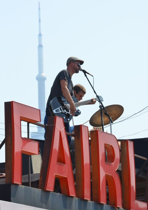 Musicians play on the rood of the Fairland grocery store in Kensington. The CN Tower is a bit hazy but it is visible in the background.