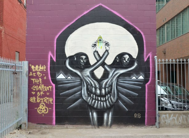 A street art painting of a large skull with the eyes painted as people's heads. Beside it are the words, Death is the conduit to rebirth
