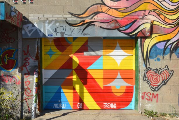 very bright coloured geometric street art on a garage door