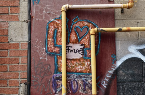 Behind two yellow pipes on the exterior of a building, a painting of a person's torso with a large heart painted on his shirt. In it's hands is a white sign with the word false written on it.