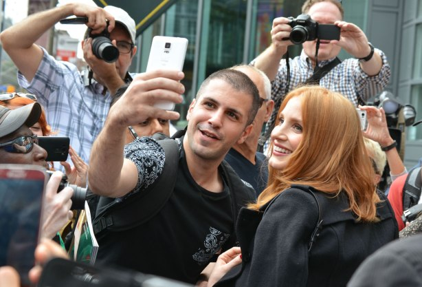 A group of fans in a crowd. One man is taking a selfie with the actress Jessica Chastain. Other people are taking photos of them.