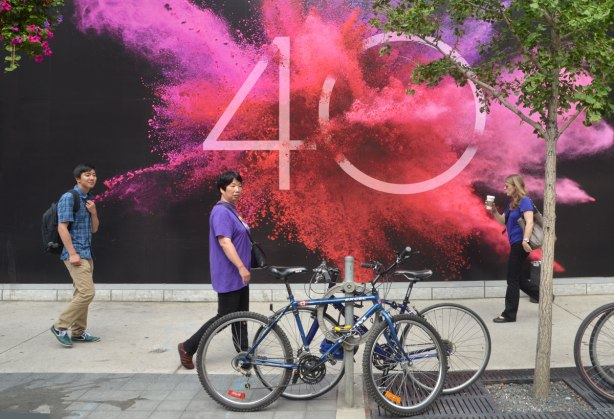 Three people walking past a bright poster for TIFF's 40th year. A burst of pink and orange colour around the number 40, all on a black background.