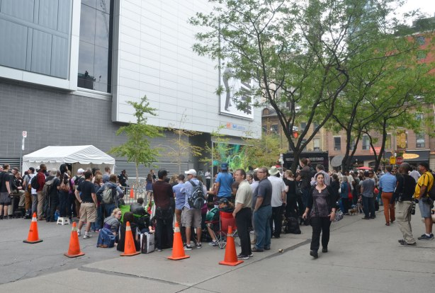 A crowd of people is waiting by the side entrance to the TIFF Lightbox theater.