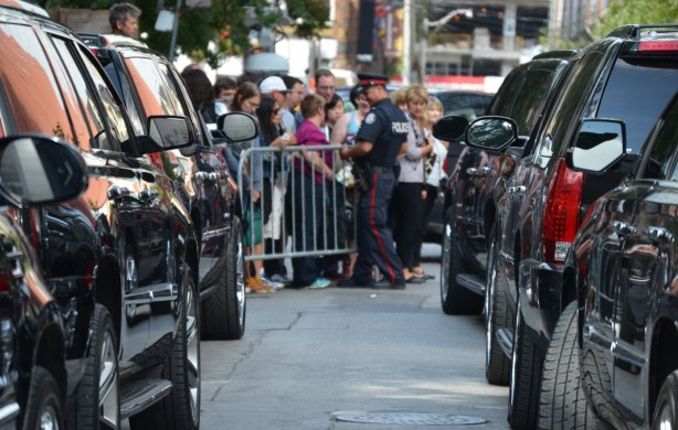 two lines of black Cadillac Escalades, looking down the lines to a group of people behind a barricade with a policeman standing with them.