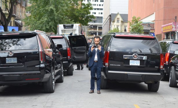 A short man is taking pictures of a crowd (directly towards the camera) or else he is taking a selfie with a lot of black Cadillac Escalades behind him.