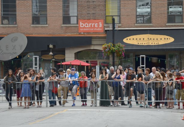 line of people waiting by a barricade at the end of a street. Queen Street west stores are in the background.