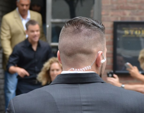 The back of the head of a security guy. His head is shaved except for the top part. He is wearing a wire. Matt Damon and another security guy are out of focus in the background.
