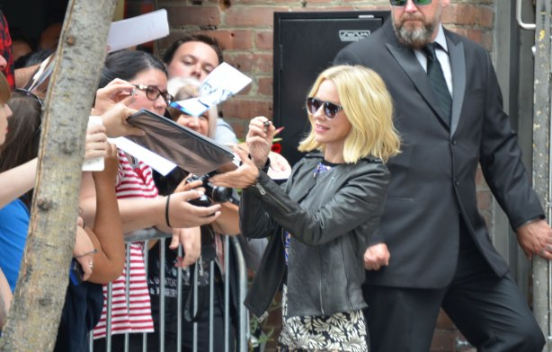Actress Naomi Watts signs autographs while a security guard looks on.