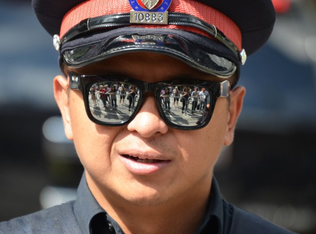 Close up of a policeman's face. He is wearing reflective sunglasses and the crowd is reflected in them.