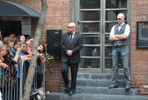 Two security guards stand on steps outside a building. One has a dark suit on, the other is wearing jeans and a grey vest. Both have shaved heads and dark sunglasses.