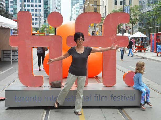 A middle aged Asian woman poses in front of the orange tiff 3D sign on King Street. A girl is sitting on the corner of it, looking off the picture to the right.