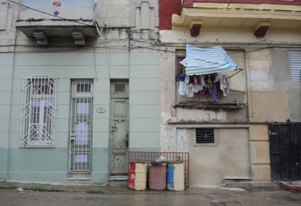 picture taken in the old part of the city of Havana Cuba - tall skinny doors at number 1104, colourful oil drums outside the door and laundry hanging from an upper window
