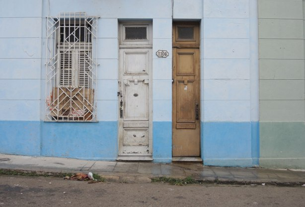 picture taken in the old part of the city of Havana Cuba - two tall skinny doors at number 1106, also a window with metal bars over it.