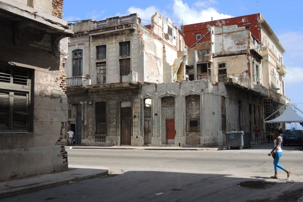 picture taken inthe old part of the city of Havana Cuba - an old dilapidated two storey building that is starting to look like it is going to fall down.  A woman is walking down the street past it