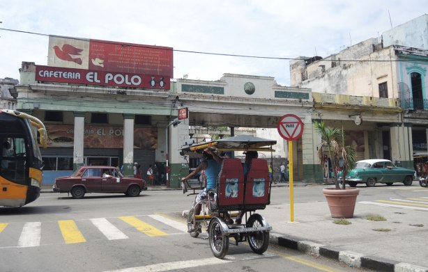 picture taken in the old part of the city of Havana Cuba -  the Cafeteria el Polo with it's red sign is across the street.  An old car is driving past, a bici (two passenger bicycle taxi) is also in the picture