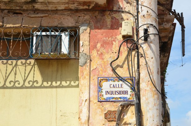 picture taken in the old part of the city of Havana Cuba - weathered building with a street sign on it, calle inquisidor, an air conditioner in the window, and a lot of electrical cables running up the side of the building