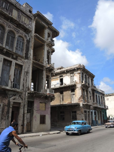 picture taken inthe old part of the city of Havana Cuba - old colonial style three storey buildings that are empty and abandoned.  Two old American cars are driving past them.
