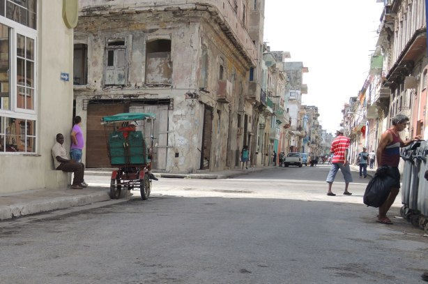 picture taken inthe old part of the city of Havana Cuba - a street scene.  A man is rumaging through garbage bins, a couple of men are sitting in doorways, some people are walking.  Old run down buildings.