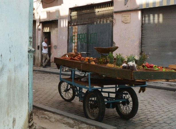 picture taken in the old part of the city of Havana Cuba - an old cart with fruit on it, a street vendor's wagon, sits on a cobblestone street with a man in a doorway in the background