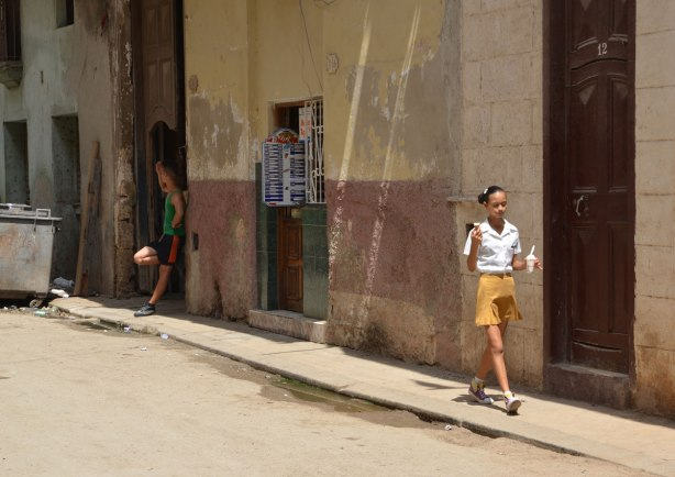 A school girl walks down a sidewalk with ice cream in her hand. A young man lounges in a doorway in the background.