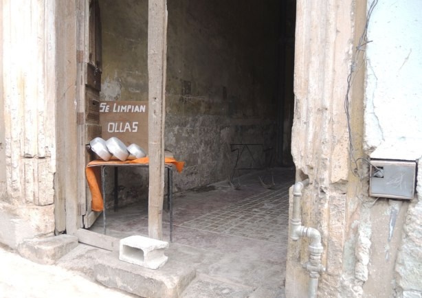 picture taken in the old part of the city of Havana Cuba - A doorway of a rather empty store.  Three bowls are on an orange cloth on a table.  The sign by the bowls says se limpian ollas (we wash bowls).