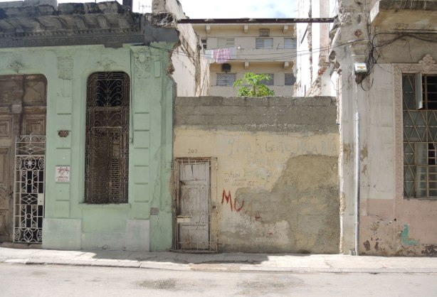 picture taken inthe old part of the city of Havana Cuba - a plain one storey structure is sandwiched between two larger more ornate buildings.