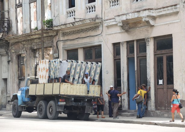 picture taken inthe old part of the city of Havana Cuba - delivering mattresses.  A truck with seven mattresses is parked in front a building.  Men are talking on the sidewalk.