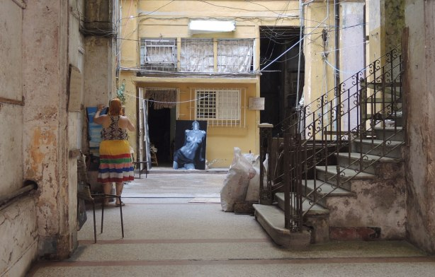 picture taken inthe old part of the city of Havana Cuba - a woman is preparing to open an art gallery store.  She is wearing a bright coloured horizontal striped skirt.  One of the paintings on display is a black and white nude woman from the thighs up