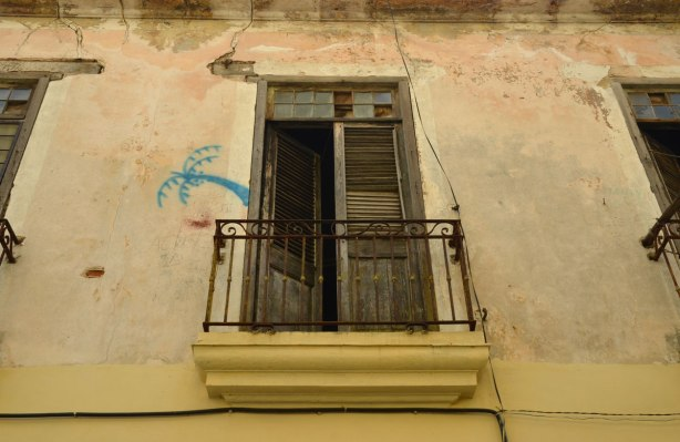 picture taken in the old part of the city of Havana Cuba - An upper storey window and small balcony. Someone has painted a small blue palm tree beside the window