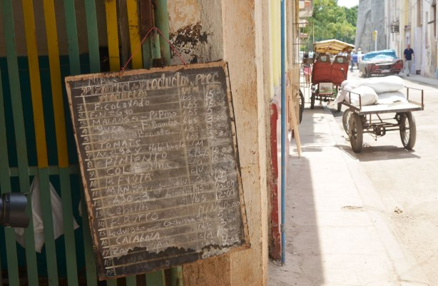 picture taken in the old part of the city of Havana Cuba - a chalk board on the doorway of a store with the prices of the merchandise that is for sale (food items)