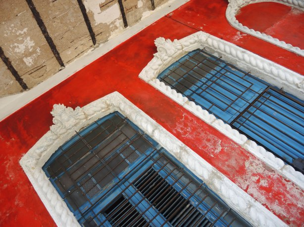 picture taken inthe old part of the city of Havana Cuba -  photo taken on an angle and looking up at the tops of two windows with ornate white window frames against a bright red wall.
